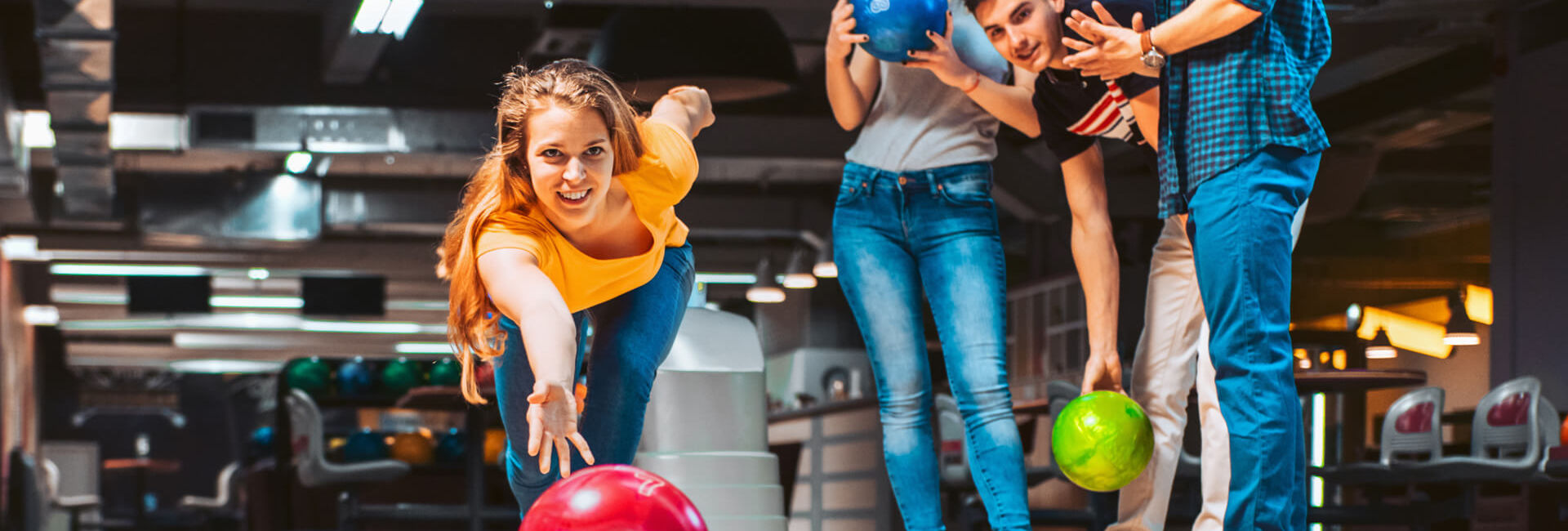 Young girl bowling with friends