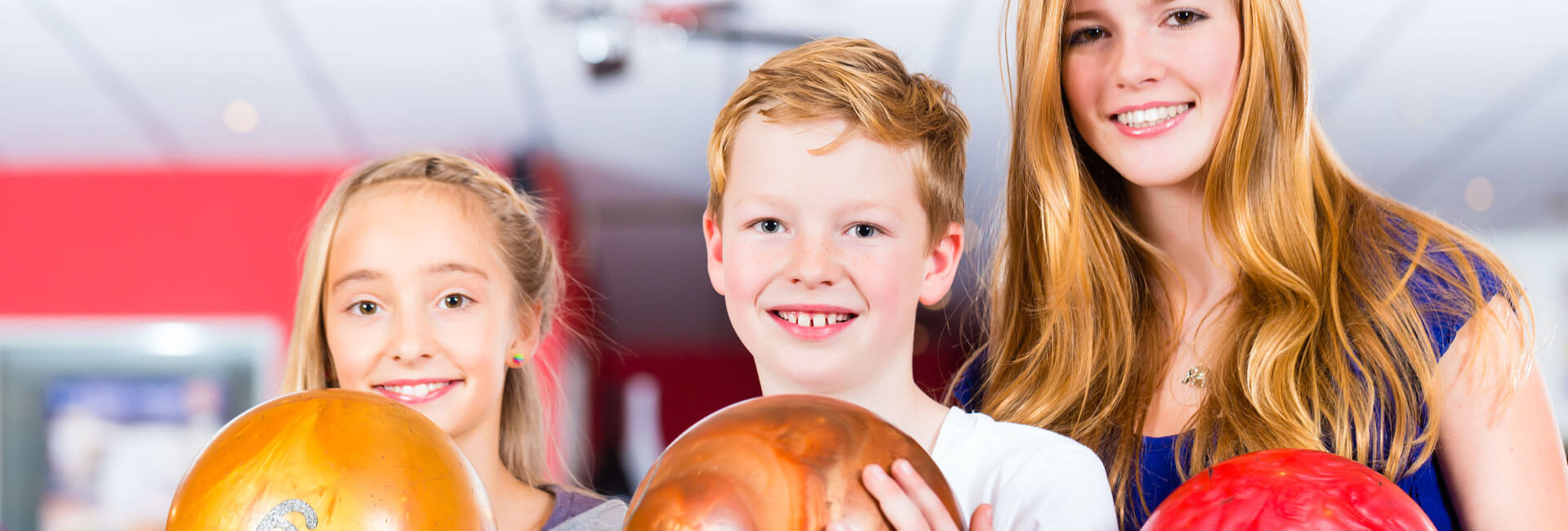 Children and teenager play bowling