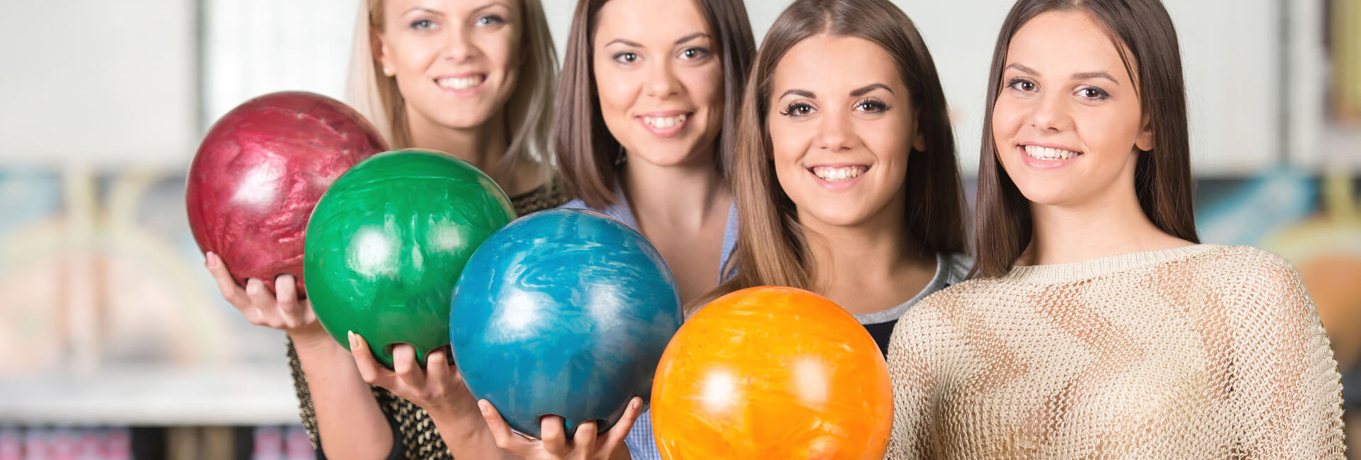 Four women holding a bowling ball