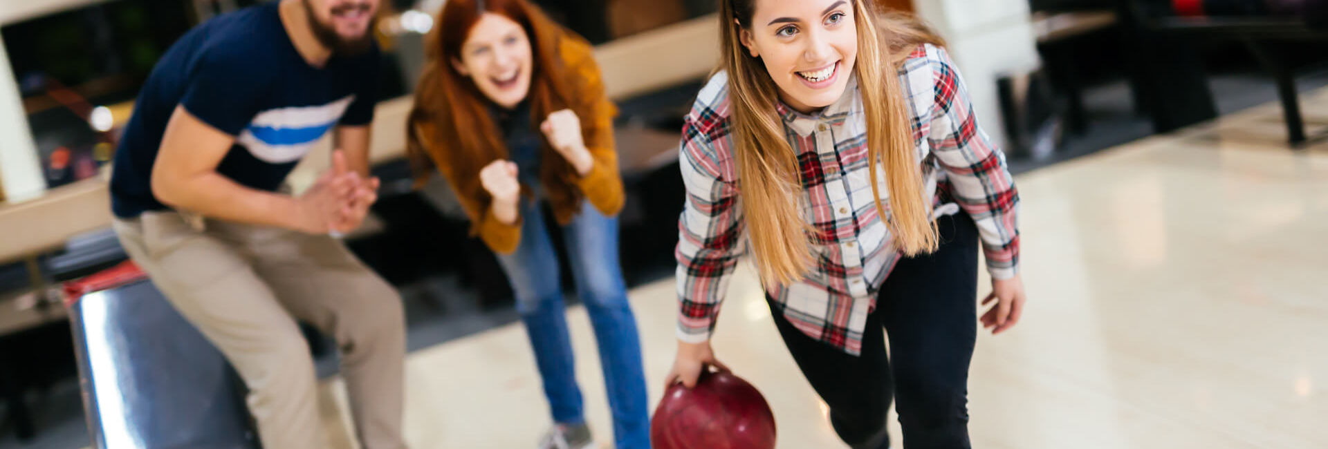 Female bowling while friends cheering